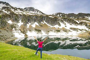 Cheerful woman with outstretched arms standing on the shores of Porcile Lakes, Tartano Valley, Valtellina, Lombardy, Italy, Europe