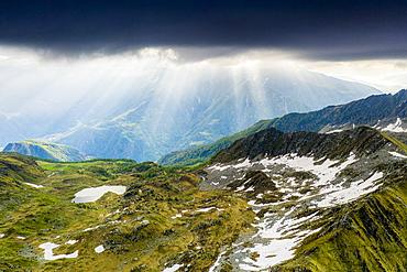 Light beam at sunrise over mountains peaks surrounding Arcoglio lake, Valmalenco, Sondrio province, Valtellina, Lombardy, Italy, Europe
