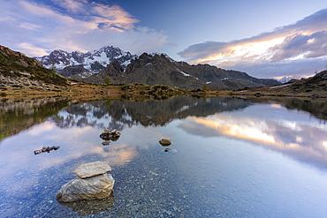Sunrise lit the rocky peak of Monte Disgrazia mirrored in the clear water of lake Zana, Valmalenco, Valtellina, Lombardy, Italy, Europe