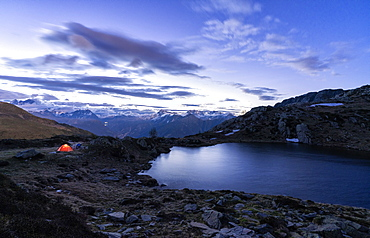 Tent of hikers on shores of the alpine lake Zana during sunrise, Valmalenco, Sondrio province, Valtellina, Lombardy, Italy, Europe