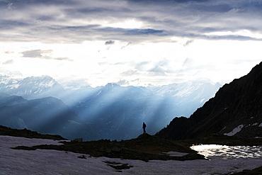 Silhouette of lone hiker admiring the sun rays at dawn over lake Zana, Valmalenco, Valtellina, Lombardy, Italy, Europe