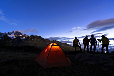 Hikers camping with tent photographing Monte Disgrazia at night, Valmalenco, Sondrio province, Valtellina, Lombardy, Italy, Europe