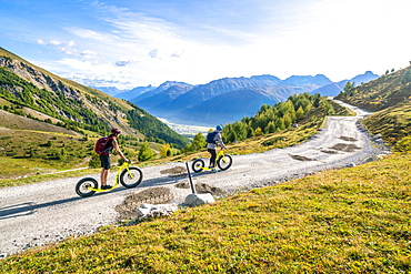 Two people having fun riding the Trottinett scooters downhill from Marguns top station to Celerina, Engadine, canton of Graubunden, Switzerland, Europe