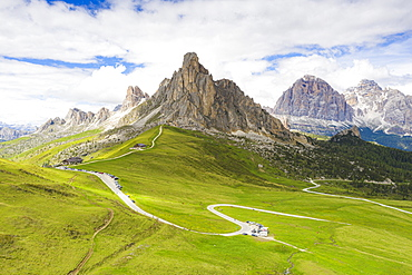 Winding road of Giau Pass in the green landscape with Ra Gusela and Tofane mountains in background, Dolomites, Veneto, Italy, Europe