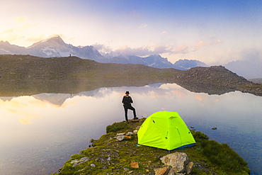Rear view of man with hat standing outside tent at Obere Schwarziseeli lake at dawn, Furka Pass, Canton Uri, Switzerland, Europe