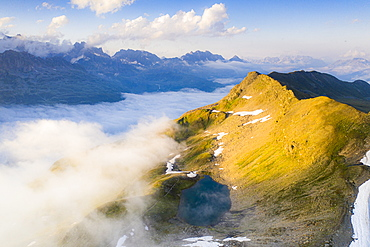 Schwarziseeli lake and Stotzigen Firsten mountain emerging from a sea of clouds, aerial view, Furka Pass, Canton Uri, Switzerland, Europe