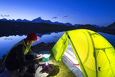 Hiker man cooking outside camping tent at Obere Schwarziseeli lake at dusk, Furka Pass, Canton Uri, Switzerland, Europe