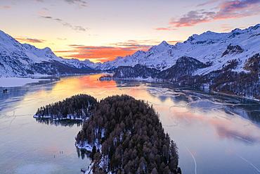 Aerial view of burning sky at sunset on frozen Lake Sils and snow capped mountains, Maloja Pass, Graubunden canton, Swiss Alps, Switzerland, Europe