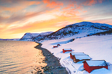 Sunset over red cabins in the snow along Porsangerfjord with North Cape (Nordkapp) on background, Troms og Finnmark, Arctic, Norway, Scandinavia, Europe
