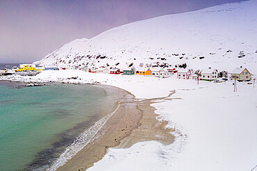 Cold sea surrounding Sorvaer village and sand beach covered with snow, Soroya Island, Hasvik, Troms og Finnmark, Arctic, Norway, Scandinavia, Europe