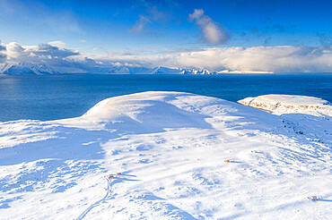 Aerial view of white mountains covered with snow surrounding the blue frozen sea, Hasvik, Soroya Island, Troms og Finnmark, Arctic, Norway, Scandinavia, Europe