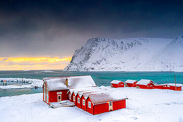 Winter sunset over the Arctic sea and fishermen cabins in the snow, Sorvaer, Soroya Island, Hasvik, Troms og Finnmark, Norway, Scandinavia, Europe