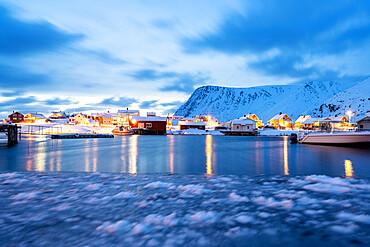 Winter dusk over the frozen sea surrounding the fishing village of Sorvaer, Soroya Island, Troms og Finnmark, Northern Norway