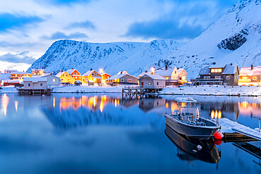 Illuminated village of Sorvaer mirrored in the cold sea during winter dusk, Soroya Island, Troms og Finnmark, Northern Norway, Scandinavia, Europe