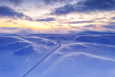 Arctic sunset over Tanafjordveien empty road crossing the snowy mountains after blizzard, Tana, Troms og Finnmark, Arctic, Norway, Scandinavia, Europe