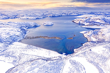 Aerial view of Norwegian County Road 98 along snowy mountains above Laksefjorden, Lebesby, Kunes, Troms og Finnmark, Arctic, Norway, Scandinavia, Europe