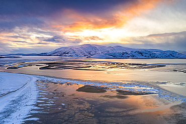 Sunset over the snow capped mountains and frozen sea in the pristine Tanamunningen Nature Reserve, Leirpollen, Finnmark, Arctic, Norway, Scandinavia, Europe