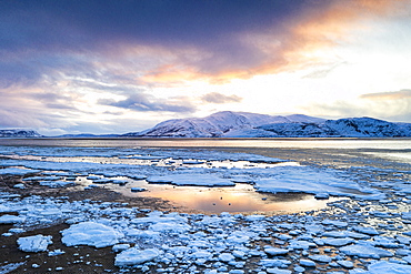 Arctic sunset on snow capped mountains and frozen sea, Tanamunningen Nature Reserve, Leirpollen, Troms og Finnmark, Arctic, Norway, Scandinavia, Europe