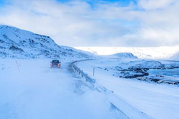 Car travelling on empty icy road along the snowy coast of cold Barents Sea, Arctic Ocean, Varanger Peninsula, Finnmark, Norway, Scandinavia, Europe
