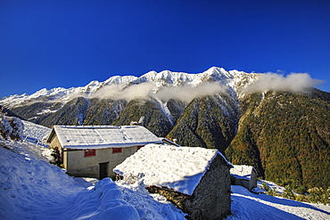 Mountain houses framed by snowy peaks, San Salvatore, Livrio Valley, Orobie Alps, Valtellina, Lombardy, Italy, Europe