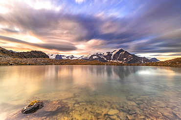 Dramatic sky at sunrise over Tresero peak reflected in lake Manzina, Valfurva, Valtellina, Sondrio province, Lombardy, Italy, Europe