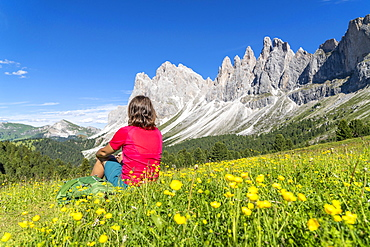 Young woman admiring the Odle peaks sitting on flowering meadows of Malga Brogles, Val di Funes, South Tyrol, Dolomites, Italy, Europe