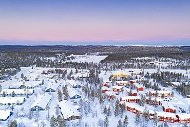 Aerial view of snow capped forest and Saariselka winter tourist resort at sunrise, Inari, Lapland, Finland, Europe