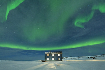 Northern Lights (Aurora borealis) on the illuminated house in the snow, Veines, Kongsfjord, Varanger Peninsula, Finnmark, Norway, Scandinavia, Europe