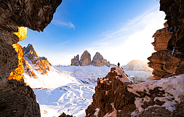 Hiker on rocks admiring Tre Cime di Lavaredo and Monte Paterno covered with snow at sunset, Sesto Dolomites, South Tyrol, Italy