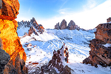 Man on rocks admiring the snowy Monte Paterno and Tre Cime di Lavaredo at sunset, Sesto Dolomites, South Tyrol, Italy