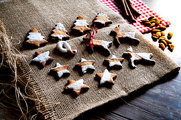 Gingerbread and butter cookies in shape of Christmas tree, stars and reindeer on canvas placemat on wood table background