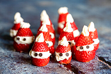Decorated cute litte strawberries in shape of Santa Claus filled with with whipped cream at Christmas