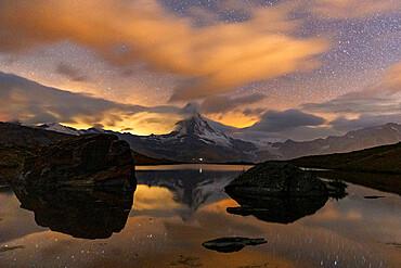 Clouds in the starry sky above Matterhorn reflected in lake Stellisee, Zermatt, Valais canton, Switzerland