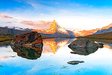 Matterhorn lit by sunrise reflected in the calm water of lake Stellisee, Zermatt, Valais Canton, Switzerland, Europe