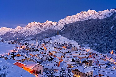 Traditional houses covered with snow during the winter dusk, Ardez, Engadine, Graubunden Canton, Switzerland, Europe