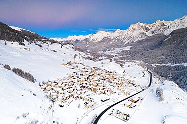 Mountain road crossing the village of Ardez covered with snow, aerial view, canton of Graubunden, Engadine, Switzerland