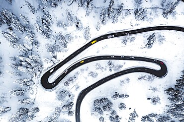Aerial view of cars driving on narrow bends of mountain road in the snow, Switzerland, Europe