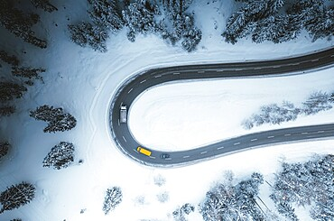 Aerial view of cars driving on bends of snowy mountain road in winter, Switzerland, Europe