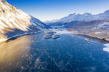 Snowcapped mountains frame the village of Sils Maria and frozen Lake Sils at sunrise, aerial view, Engadin, Switzerland