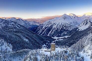Sunrise on ancient Torre Del Belvedere tower and snowy woods, Maloja, Bregaglia, Graubunden canton, Engadin, Switzerland