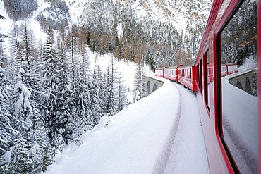 Bernina Express train in the alpine landscape covered with snow, Preda Bergun, Albula Valley, Graubunden Canton, Switzerland, Europe