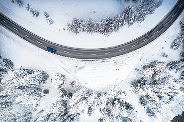 Car driving on bends on snowy mountain road from above, Switzerland, Europe