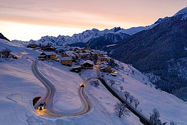 Cars driving on hairpin bends of snowy road at dawn, Guarda, Graubunden canton, Lower Engadin, Switzerland