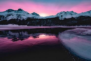 Colorful sky at sunrise on snowcapped mountains and frozen Lake Silvaplana, Maloja, Engadine, Graubunden canton, Switzerland, Europe