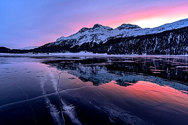 Winter sunrise on snowcapped mountains mirrored in the icy Lake Silvaplana, Maloja, Engadine, Graubunden canton, Switzerland, Europe