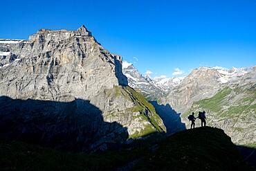 Two hikers admiring mountains during the hike towards Muttsee Hut on Kalktrittli path, Canton of Glarus, Switzerland, Europe