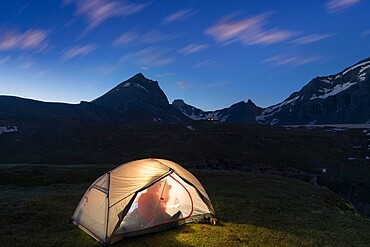 Silhouette of hiker inside the illuminated tent above lake Limmernsee at dusk, Canton of Glarus, Switzerland