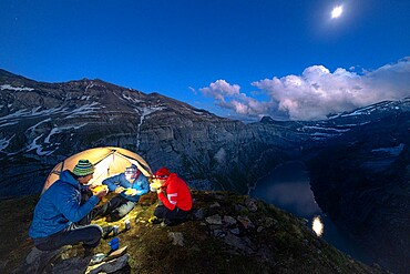 Three men hikers enjoying dinner outside a tent above lake Limmernsee at dusk, Canton of Glarus, Switzerland, Europe