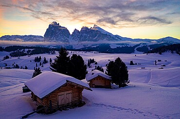 Wood cabins covered with snow with Sassopiatto and Sassolungo in background at dawn, Seiser Alm, Dolomites, South Tyrol, Italy, Europe