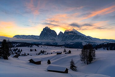 Mountain huts covered with snow with Sassopiatto and Sassolungo in background at dawn, Seiser Alm, Dolomites, South Tyrol, Italy, Europe